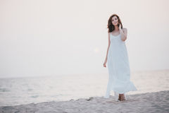 Young beautiful woman in a white dress walking on an empty beach near ocean Stock Image