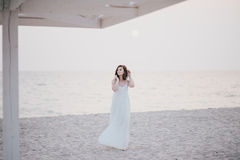 Young beautiful woman in a white dress walking on an empty beach near ocean Stock Photo
