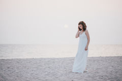 Young beautiful woman in a white dress walking on an empty beach near ocean Royalty Free Stock Photo