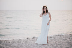 Young beautiful woman in a white dress walking on an empty beach near ocean Stock Images