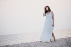 Young beautiful woman in a white dress walking on an empty beach near ocean Stock Photos