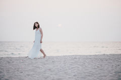 Young beautiful woman in a white dress walking on an empty beach near ocean Stock Photography