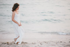 Young beautiful woman in a white dress walking on an empty beach near ocean Royalty Free Stock Image