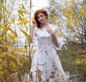 Young woman in white dress among yellow leaves in autumn. Young beautiful woman in white dress among yellow leaves in autumn in forest Royalty Free Stock Photo