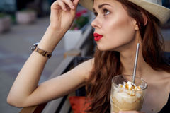 Young beautiful woman in a white hat holds a latte outdoors in the city Stock Photos