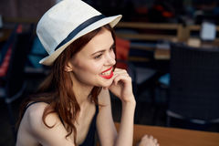 Young beautiful woman in a white hat sits in a cafe on the street on a summer terrace Royalty Free Stock Photos
