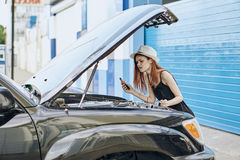 Young beautiful woman in a white hat trying to fix a car in the summer in the city stock image