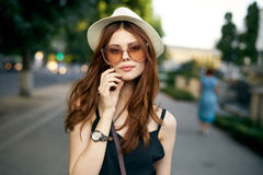 Young beautiful woman in a white hat and wearing sunglasses walking along the main street in the city stock photo