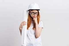 Young beautiful woman in a white helmet on a light background holds blueprints, engineer, construction Stock Photos