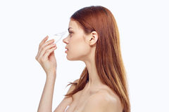 Young beautiful woman on white isolated background burying her eyes with eye drops.  royalty free stock photo