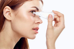 Young beautiful woman on white isolated background dripping in the eyes eye drops.  royalty free stock photography