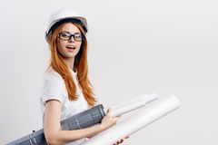 Young beautiful woman on white isolated background holds blueprints, designer, engineer Stock Image