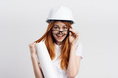 Young beautiful woman on white isolated background holds blueprints, engineer, designer Royalty Free Stock Image