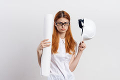 Young beautiful woman on white isolated background holds drawing and hard hat, designer, construction, engineer Royalty Free Stock Photos