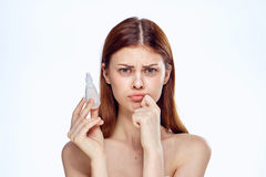 Young beautiful woman on white isolated background holds eye drops.  royalty free stock photos