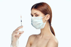 Young beautiful woman on white isolated background in medical mask holds syringe, portret, medicine, plastic surgery Royalty Free Stock Photography