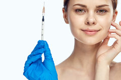 Young beautiful woman on white isolated background in rubber gloves holds syringe, medicine, plastic surgery Stock Images