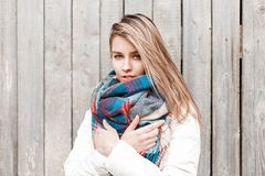 Young beautiful woman in a white jacket and scarf posing. Near a gray wooden wall royalty free stock photo