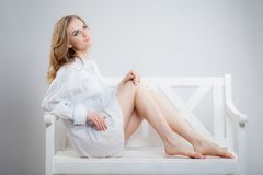 Young beautiful woman in a white men`s shirt is sitting on a white bench