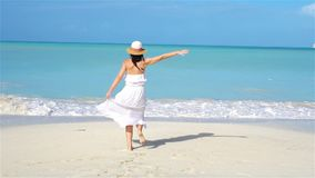 Young beautiful woman on white sand tropical beach. Caucasian girl with hat background the sea. SLOW MOTION stock video