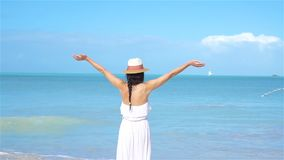 Young beautiful woman on white sand tropical beach. Caucasian girl with hat in white dress background the sea stock video