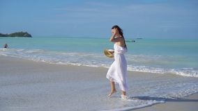 Young beautiful woman on white sand tropical beach. Caucasian girl with hat in white dress background the sea stock footage