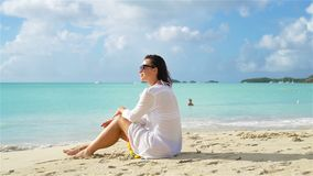 Young beautiful woman on white sand tropical beach. Caucasian girl sitting on the whitesnow sand with beautiful view stock footage