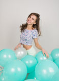 Young beautiful woman in white shorts and colorful top playing with balloons , slow motion Stock Photo