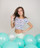 Young beautiful woman in white shorts and colorful top playing with balloons , slow motion Royalty Free Stock Images