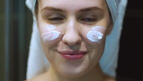 Young beautiful woman with a white towel on her head applying moisturising cream on her face. Concept. Close up of a