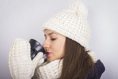 Young beautiful woman in winter warm clothes with black cup Stock Photo