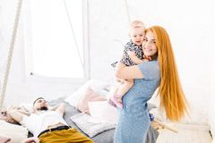 Free Young Beautiful Woman With Red Long Hair In A Blue Dress Holds A Child On Her Hands One Year Blonde Near The Bed On Which Lies A M Stock Image - 104795361