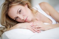 A young beautiful woman is lying in her bed. royalty free stock images