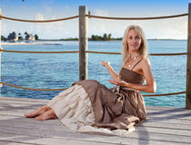 Young beautiful woman  on a wooden platform over  the sea Stock Photos
