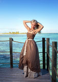 Young beautiful woman  on a wooden platform over  the sea Stock Image