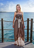 The young beautiful woman  on a wooden platform over  the sea Stock Image