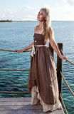 The young beautiful woman  on a wooden platform over  the sea Stock Photos