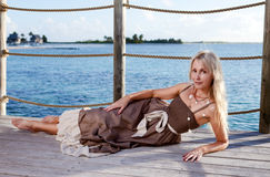 The young beautiful woman  on a wooden platform over  the sea Stock Photo