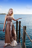 The young beautiful woman  on a wooden platform over  the sea Stock Images