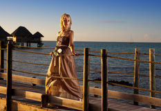 Young beautiful woman  on a wooden platform over  the sea Royalty Free Stock Image