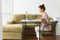 Young Beautiful Woman Work from Home Office. Young beautiful woman working at her home office Communication computer internet laptop Businesswoman entrepreneur royalty free stock image