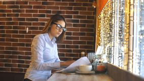 Young beautiful woman working in coffee shop , using computer laptop about business work. Young businesswoman on a coffee break. Using laptop stock video footage