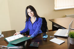 Young beautiful woman working with documents in the workplace in the office Royalty Free Stock Image
