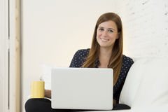Young beautiful woman working with laptop computer smiling happy or doing online internet shopping Royalty Free Stock Image