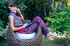 Young beautiful woman working with laptop at outdoor tropical park, smile and happy relaxing feeling in the morning. Freelancer working businesswoman lifestyle Stock Images