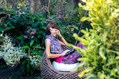 Young beautiful woman working with laptop at outdoor tropical park, smile and happy relaxing feeling in the morning Royalty Free Stock Photography