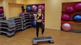 Young beautiful woman working out with stepper in gym. stock video footage