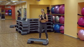 Young beautiful woman working out with stepper in gym, slow motion. stock video footage
