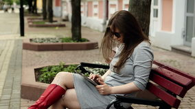 Young beautiful woman working on tablet computer sitting on bench outdoors stock video