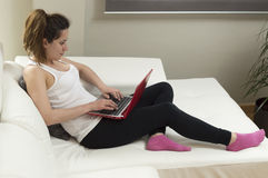 Young beautiful woman working using laptop on sofa at home Stock Photos